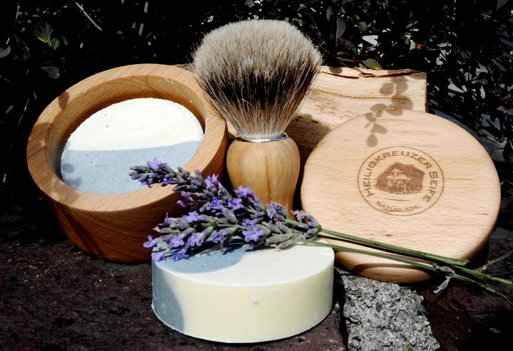 Mit dem Duft der Provence: Eine sanfte Rasierseife mit Lavendelduft und pflegender Sheabutter. Im Bild: Rasierseife im Buchenholztiegel, Nachfüllstück (vorn), Dachshaar-Rasierpinsel mit Olivenholzgriff.