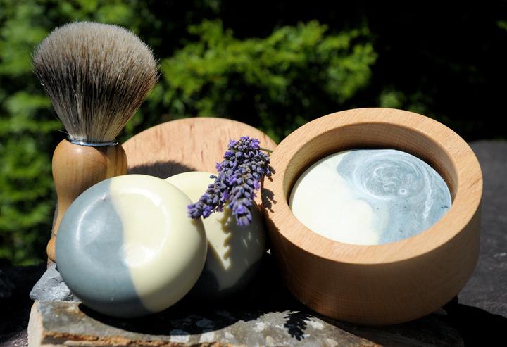 """Mit dem Duft der Provence: Eine sanfte Rasierseife mit Lavendelduft pflegender Sheabutter. Im Bild Rasierpinsel mit Olivenholzgriff, Rasierseife in der Variante """"Rundling"""" und im Buchenholztiegel."""