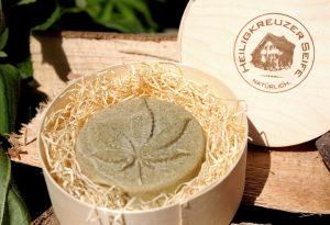 Blumiges Geschenk: Vegane Hanfseife auf Holzwolle in der Spandose.